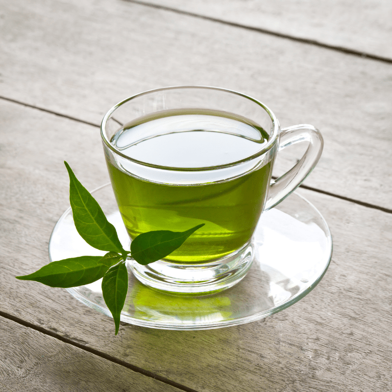A cup of Green Tea on a wooden board