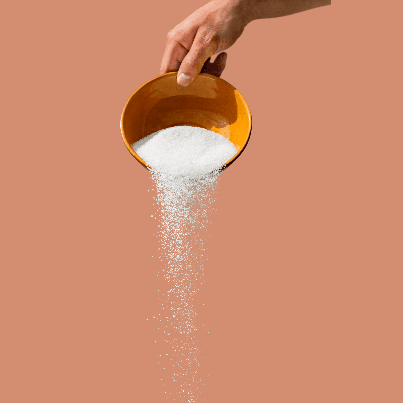 Salt poured mid flow from a hand holding a bowl