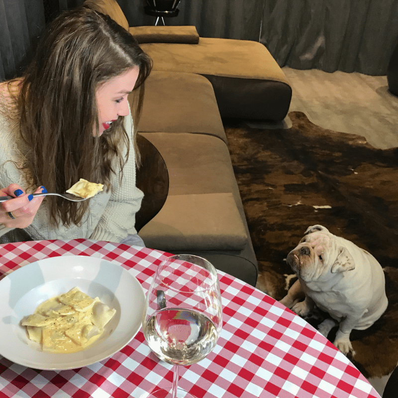Young woman eating pasta with a dog watching