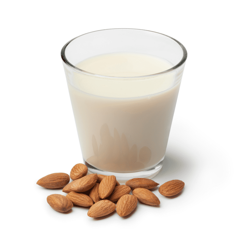 Glass of Almond milk with a heap of almonds on white background