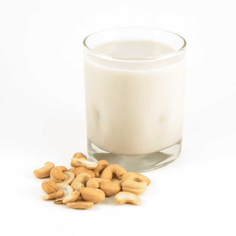 A cold glass of cashew milk next to a pile of cashews isolated on a white background.