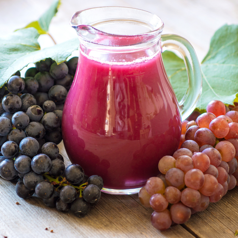 Fresh Grape Juice in a jug with bunches of grapes around it