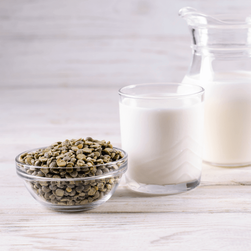 Vegetable pea milk in a milk jug and peas in a glass jar. Gluten-free, lactose-free product.