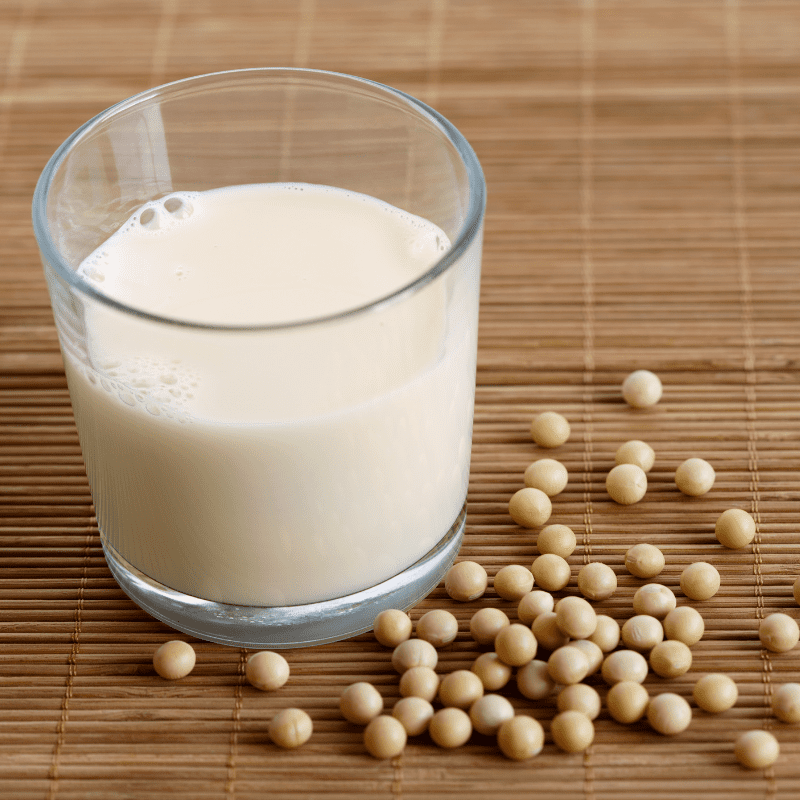 Glass of soya milk with froth on bamboo mat with spilled soya beans.
